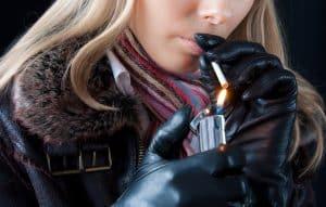 Junge Frau zündet Zigarette mit Feuerzeug