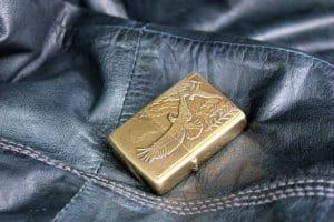 Goldenes Benzinfeuerzeug auf ledernen Untergrund