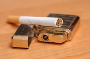 Zigarette und goldenes Feuerzeug