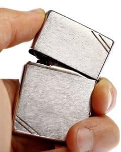 Mann hält Pfeifenfeuerzeug aus Metall in Hand