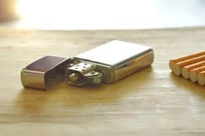 Goldenes Feuerzeug auf Holztisch