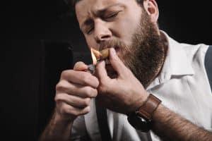 Mann zündet sich eine Zigarre an