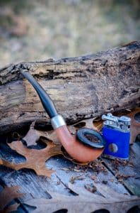 Pfeife und Feuerzeug im Wald