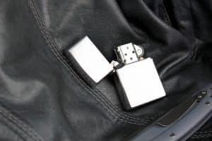 Silbernes Benzinfeuerzeug auf Lederjacke