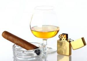Goldenes Feuerzeug mit Whiskeyglas und Zigarre