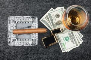 Zigarre und Whiskey mit Feuerzeug und Geld